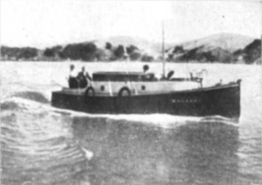 A sepia photo, taken in the early 1900s, of a 30 foot fishing boat, with two people on board and heading along the coast in the Bay of Islands