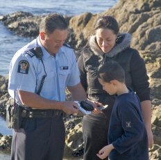 Fishery Officer measuring paua